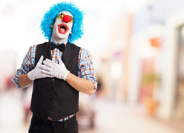 Clown with mouth open and hands on chest Free Photo