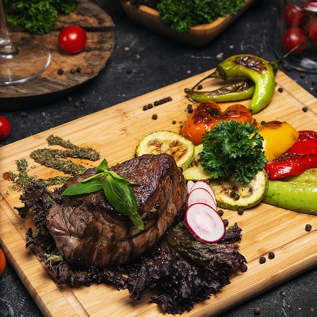 Club beef steak with pepper sauce and grilled vegetables on cutting board Free Photo