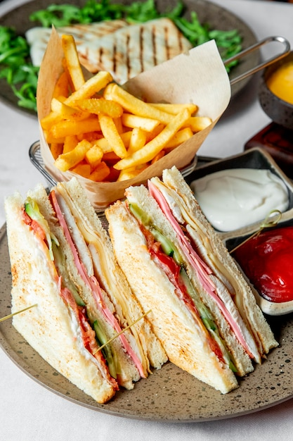 Club sandwich served with french fries ketchup and mayonnaise Free Photo