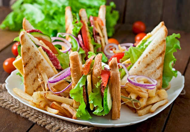 Club sandwich with cheese, cucumber, tomato, smoked meat and salami. served with french fries. Free Photo