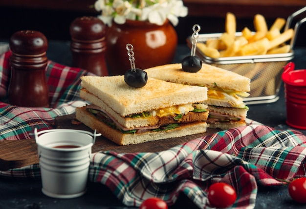 Club sandwich with eggs, lettuce, salami, cucumber, tomato, served with fries Free Photo