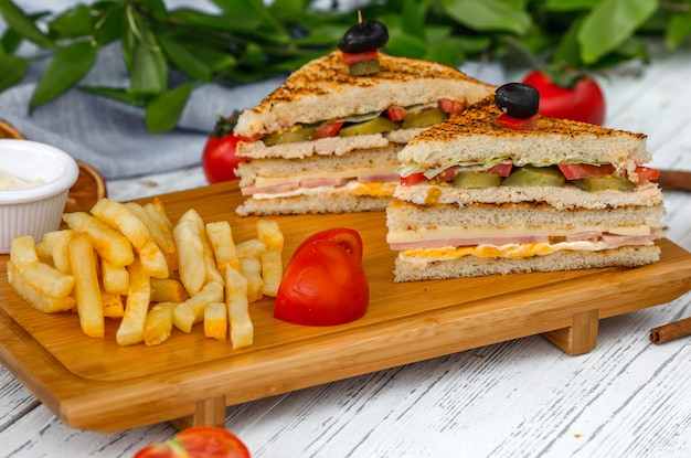 Club sandwich with french fries on wooden board Free Photo