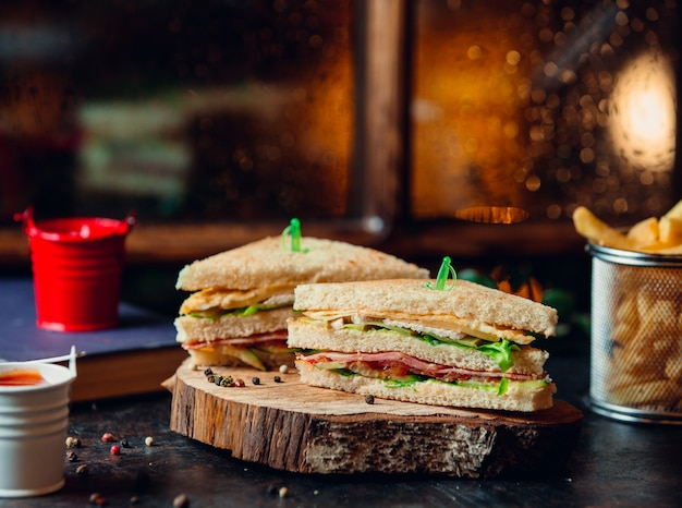 Club sandwich with ham, lettuce, tomato, cheese, and fries on wooden board Free Photo
