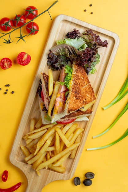 Club sandwich with side herbs and fries _ Free Photo