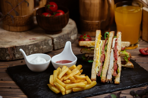 Club sandwiches in toast with french fries and sauces. Free Photo