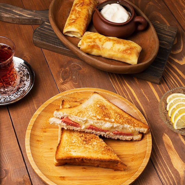 Club sandwiches with salami, bacon and blinchik served with yogurt in wooden plate with tea Free Photo