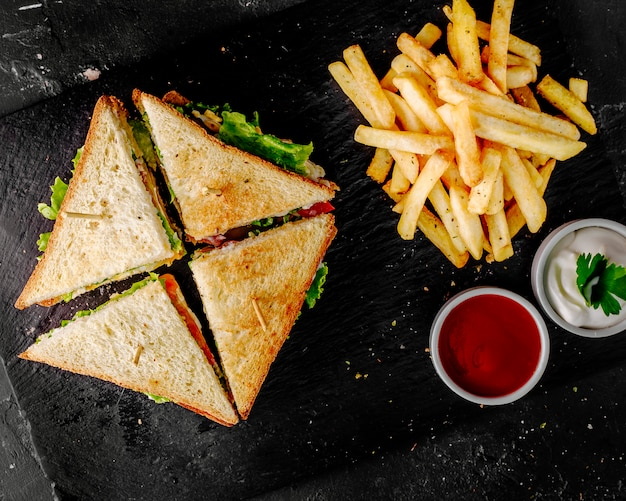 Club sandwiches with tomato ketchup,mayonnaise and potatoes. Free Photo