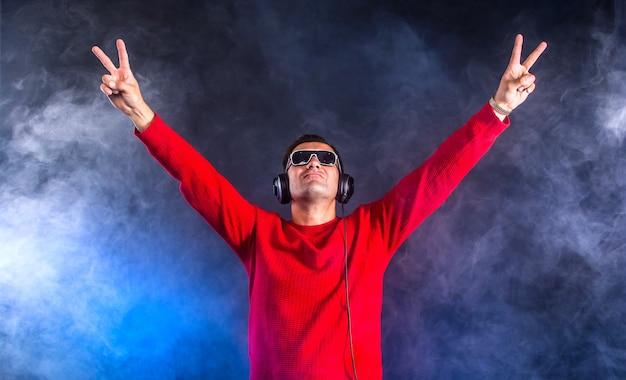 나이트 클럽에서 위로 손으로 헤드폰에 Clubber Dj 프리미엄 사진