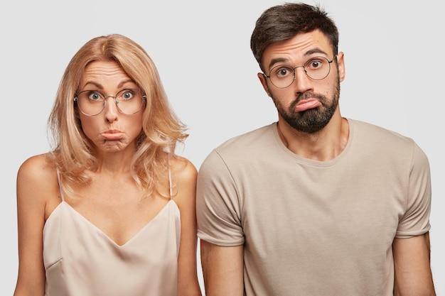 無知な疑わしい家族のカップルが戸惑い、口すぼめ呼吸で肩をすくめる、どこで休暇を過ごすのかわからない 無料写真