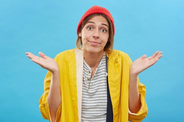 Бестолковая девочка-подросток в красной стильной шляпе и желтом плаще смотрит с широко раскрытыми глазами, пожимая плечами в невежестве или безразличии, и говорит: «вещи случаются» Бесплатные Фотографии