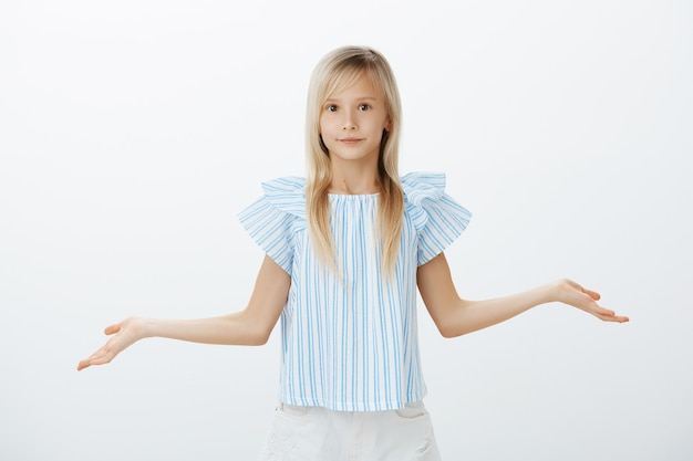 Clueless troubled little girl with blond hair in trendy blue blouse, spreading hands and shrugging with confused and unaware expression, being unable to answer over gray wall Free Photo