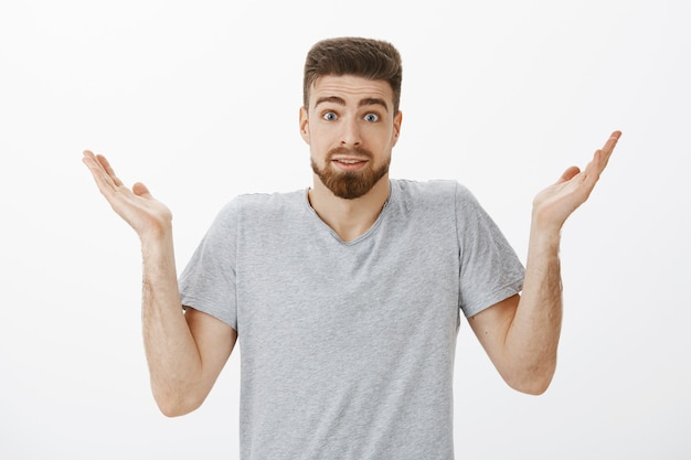 Clueless unaware handsome bearded man shrugging with raised hands and eyebrows making silly clueless expression cannot answer question being confused over gray wall Free Photo