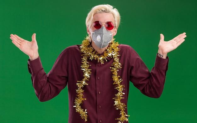 Clueless giovane uomo biondo con gli occhiali e maschera protettiva con tinsel ghirlanda intorno al collo guardando la telecamera che mostra le mani vuote isolate su sfondo verde Foto Gratuite