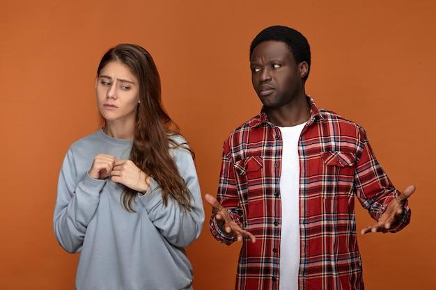 Бестолковый молодой парень африканской национальности, потерявшись, глядя на свою девушку с растерянным выражением лица, совершенно не может ее понять. неуверенная белая женщина недовольна своим парнем Бесплатные Фотографии