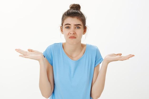 Бестолковая молодая женщина пожимает плечами и гримасничает, ничего не знаю Бесплатные Фотографии