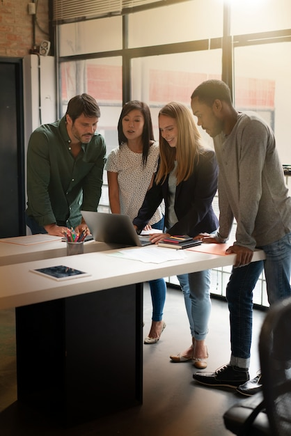 Co workers standing over desk going through presentation on computer Premium Photo