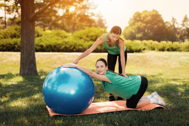 Coach helps a woman in a green t-shirt doing yoga exercises. Premium Photo
