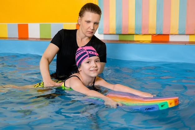 Тренер учит ребенка в закрытом бассейне плавать и нырять. концепция обучения Premium Фотографии