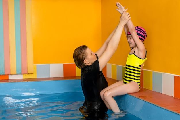 Тренер учит ребенка в крытом бассейне плавать и нырять Premium Фотографии
