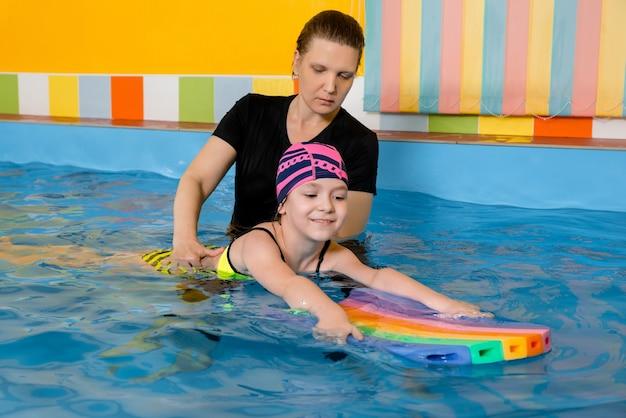 Тренер учит ребенка в крытом бассейне плавать с флаттер-доской Premium Фотографии
