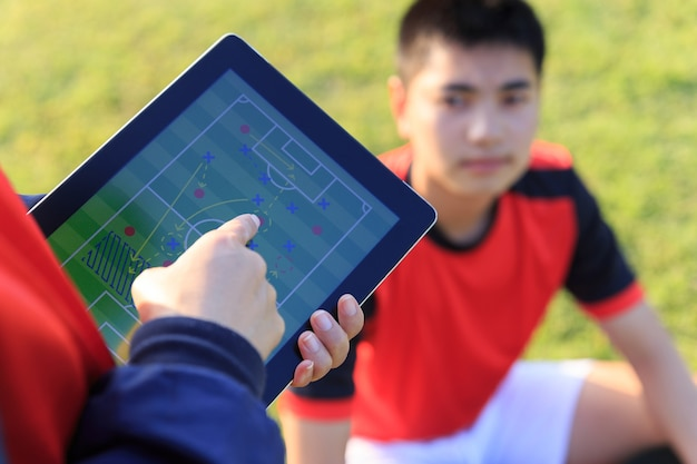 Coach training a tactic for asian teenager football player. Premium Photo