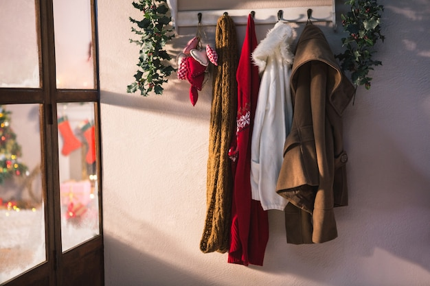 Coat rack with hanging winter clothes Free Photo