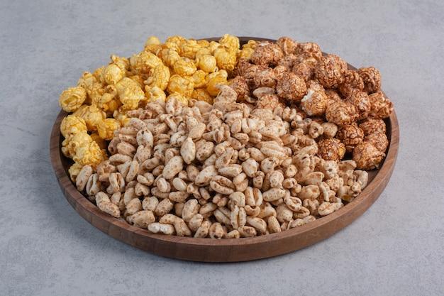 Caramelle e fiocchi di popcorn ricoperti su un vassoio su marmo. Foto Gratuite