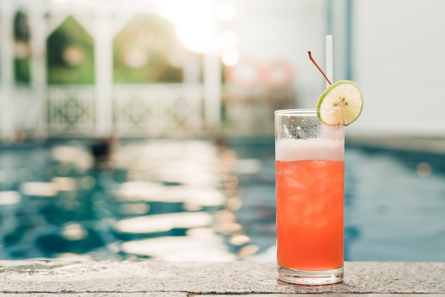 Cocktail at the edge of the swimming pool. red cocktail with an orange slice on the background of the swimming pool. vintage effect style pictures. Free Photo