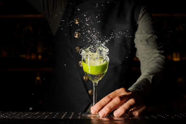 Cocktail glass with splashing alcoholic drink and lime in it Premium Photo