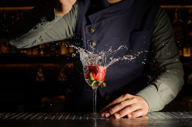 Cocktail glass with splashing drink and rose in it Premium Photo