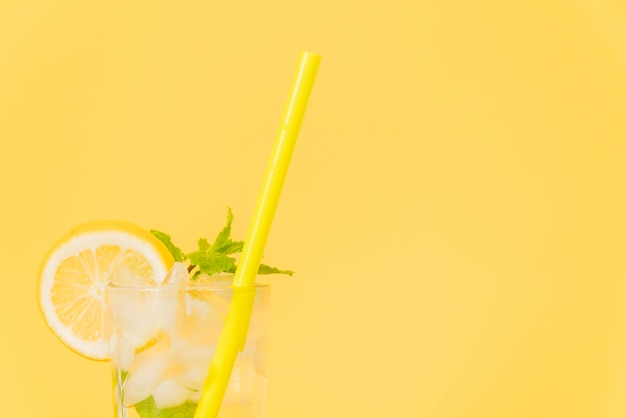 Cocktail glass with straw and lemon on yellow background Free Photo