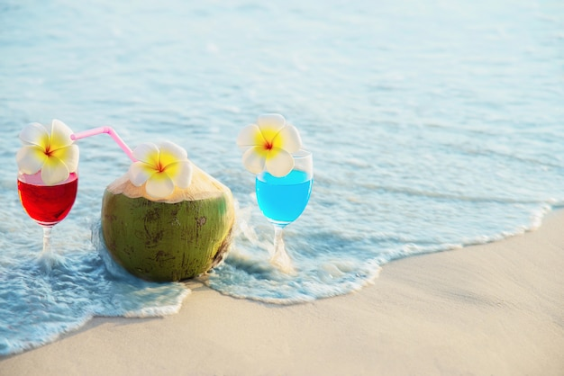 Cocktail glasses with coconut and pineapple on clean sand beach - fruit and drink on sea beach Free Photo