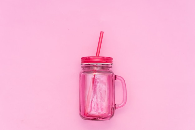Cocktail in mason's pink mug on yellow background with shells Premium Photo