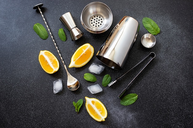 Cocktail shaker and bar tools. ingredients for a cold alcoholic cocktail. mojito cocktail. lemon, mint, ice, rum. top view, horizontal, black background, copy space Premium Photo