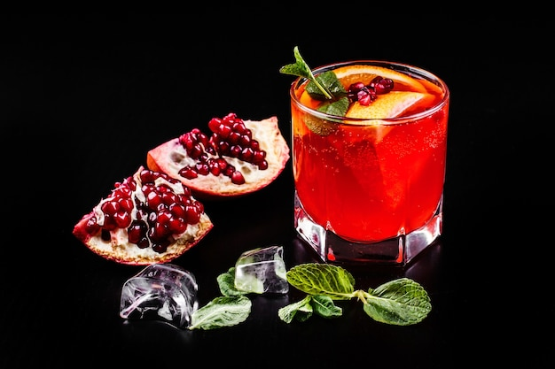 Cocktail of vodka, grenadine, pomegranate, ice and mint stands on a black table Free Photo
