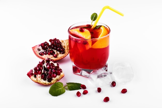 Cocktail of vodka, grenadine, pomegranate, ice and mint stands on a white table Free Photo