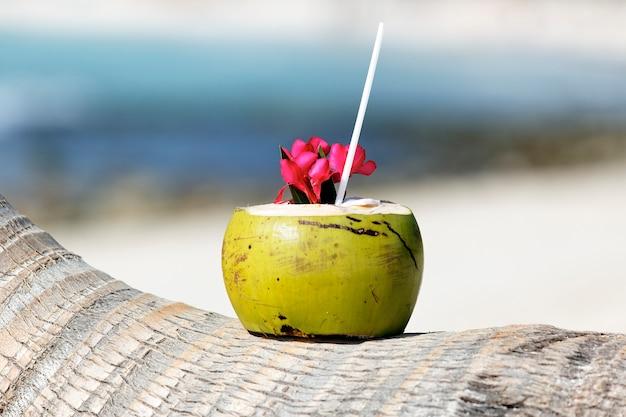 カリビアンビーチのヤシの木にストローを飲みながらカクテル 無料写真