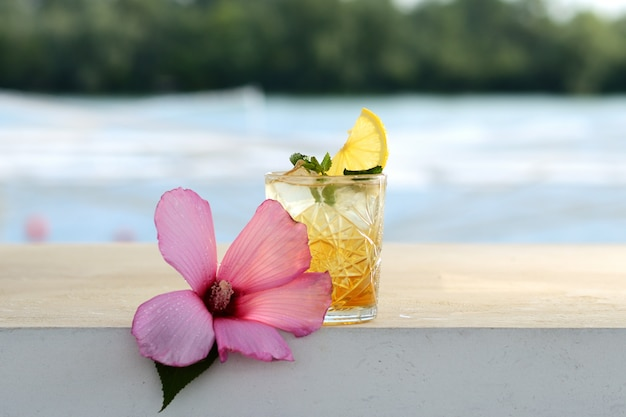 Cocktail with lemon and mint in a glass. with flower decor Premium Photo
