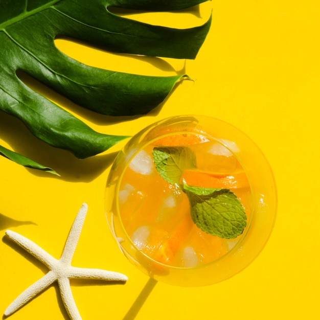 Cocktail with orange, mint and ice near sea star Free Photo