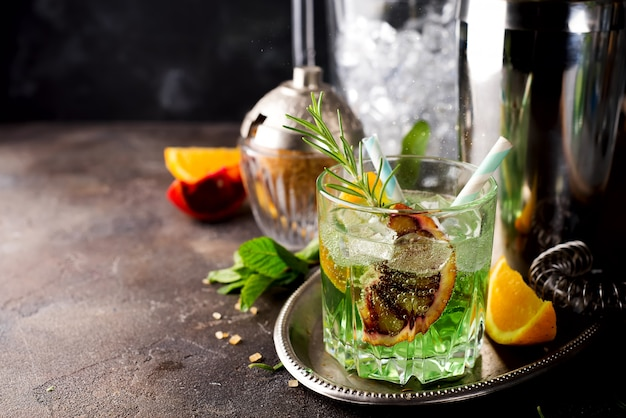 Cocktail with red lemon mint and vodka on dark stone background Premium Photo