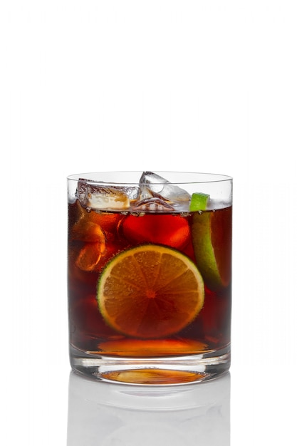 Cocktail with rum and cola with ice, lime and lemon in oldfashioned glass isolated on white Premium Photo