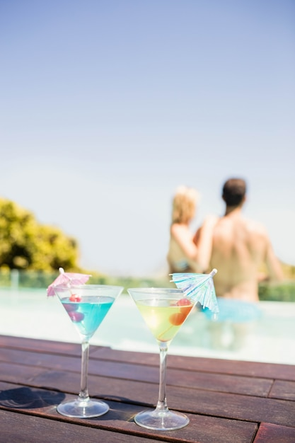 Cocktails on pools edge and couple in the pool Premium Photo