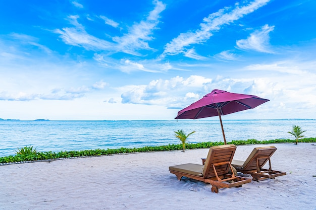 空の椅子デッキと傘とビーチ海海の美しい風景は、白い雲と青い空とほぼcoco子の木 無料写真