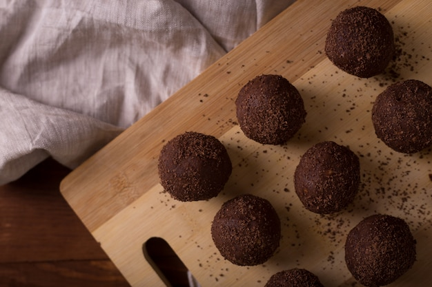 Cocoa balls, chocolate truffles cakes on board on wooden table Premium Photo
