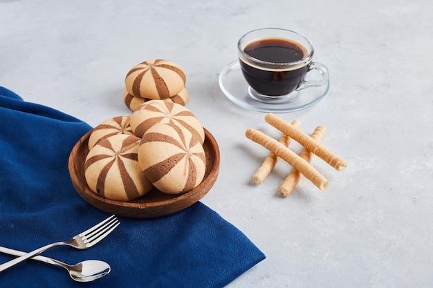 ココアクッキーのパンとワッフルは、青いテーブルクロスにコーヒーを入れてスティックします。 無料写真