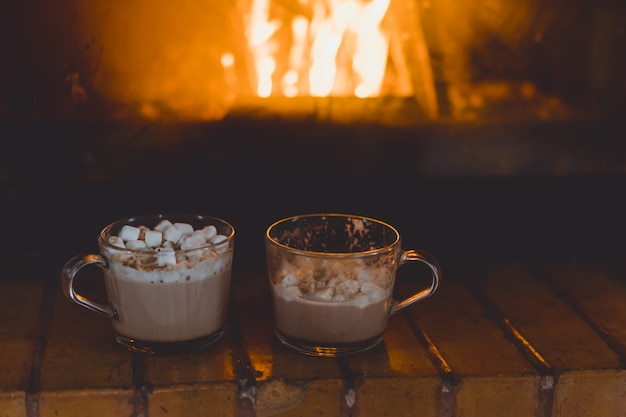 Cocoa mugs with marshmallows near the fireplace. Free Photo