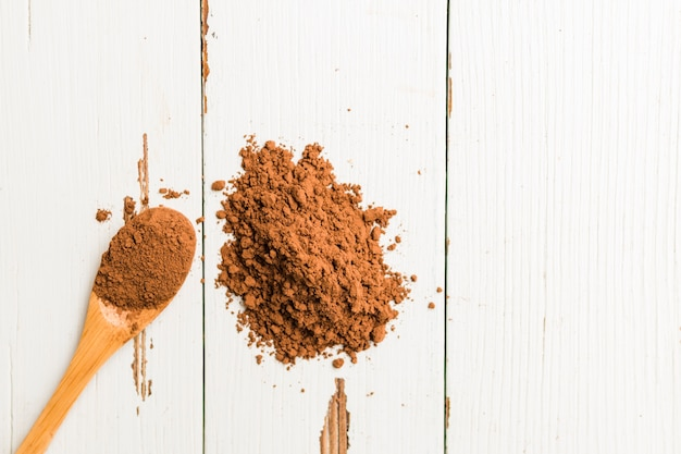 Cocoa powder poured out wooden spoon Free Photo