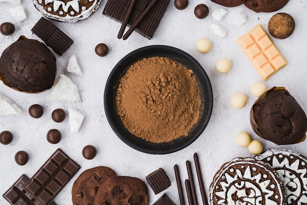 Cocoa powder with chocolate items on white backdrop Free Photo