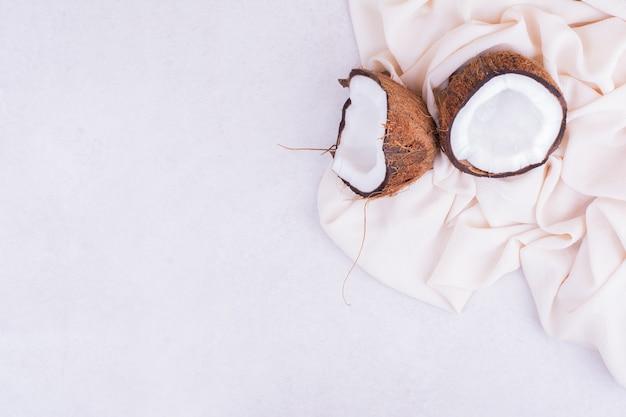 Кокос, разбитый на две части, на бежевой скатерти Бесплатные Фотографии