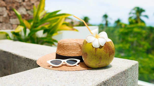 Coconut cocktail decorated plumeria, straw hat and sunglasses on the table. Free Photo